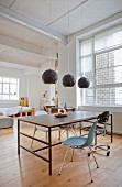 Dining table and various chairs in urban loft apartment