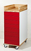 Renovated chest of drawers with red fronts on castors