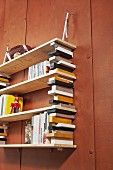 Bookcase made from colourful blocks hung on wall