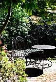 Spindly metal bench and table in sunny garden