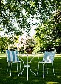 Zwei weisse, filigrane Metallstühle mit Kissen um runden Tisch auf Rasen im Garten
