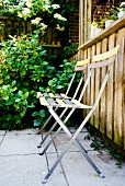 Delicate folding chairs on terrace next to wooden balustrade