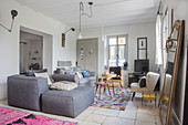 Grey armchair with matching stool and retro armchair around side tables in living area in patterned rug on tiled floor