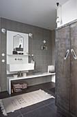 Badezimmer mit weißem Waschtischelement und eingebautem Schrank mit Metalltüren