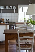 Old wooden table below white pendant lamp in modern kitchen with white counter against grey wall