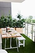 Gedeckter Tisch und weisse Sitzbank auf Balkon mit Kunstrasenteppich, im Hintergrund Nadelbäumchen in Holzkisten gepflanzt