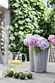 Purple and pink hydrangeas in grey vase, glass jug of lemonade and fresh figs on wooden table
