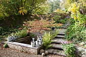 Watering cans on edge of pond and steps in autumnal garden