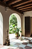 Antique candlesticks and house plant in loggia with chequered floor