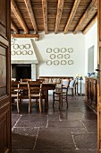 Wooden table and chairs in traditional dining room with rustic stone floor and wood-beamed ceiling