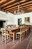 Long wooden table and chairs on rustic stone floor below glass chandelier hung from wood-beamed ceiling in dining room