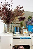 Dishes, books and flowers on old kitchen furniture