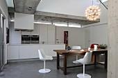 weiße Schalenstühle um rustikalen Holztisch in offener Küche mit Betondecke