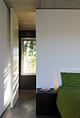 Bed against white partition with swing door in minimalist bedroom