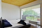 Minimalistisches Schlafzimmer mit Panoramafenster und Holzdecke