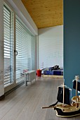 Model boat against blue partition wall and view into minimalist child's bedroom in designer apartment