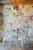 Round table and metal chairs in front of floral wallpaper