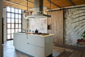 Modern island counter with hob below extractor hood in rustic kitchen