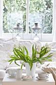 Weisser Tulpenstrauss auf Kaffeetisch vor gemütlicher Couch