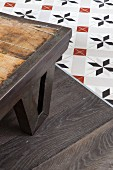 Corner of table with metal frame and metal frame on parquet floor adjoining ornamental floor tiles