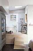 View from bedroom into open-plan bathroom with free-standing bathtub and rustic washstand on platform accessed via steps