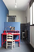 Wooden chair and red desk against blue half-height wall in front of shower area