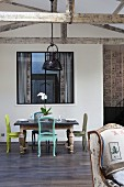 Antique chairs painted in various colours around table in front of interior window in loft-style interior with wooden half-timber beams
