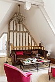 Pink armchairs and brown leather sofa in attic lounge