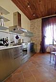 Modern stainless steel kitchen with terracotta floor tiles
