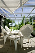 White plastic chairs and stools with seat cushions below awning in conservatory