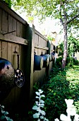 Old saucepans hung on garden fence
