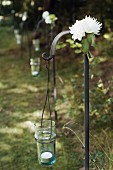 Row of wrought iron hooks decorated for wedding with flowers and candle lanterns