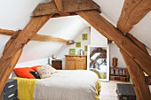 Rustic roof beams in attic bedroom