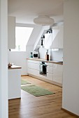 Open-plan kitchen with sloping ceiling