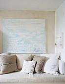 Sitzbank mit Kissen in Weiss und Naturfarben, vor Wand mit modernem Bild