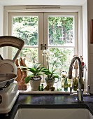 Detail of kitchen counter with sink below window and vintage kitchen scales to one side