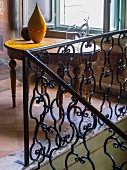 Wrought iron balustrade and antique wooden table in palazzo with terracotta floor