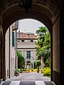 View through arch into Mediterranean courtyard with open gate