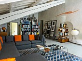 Living room with sloping ceiling, exposed beams, grey sofa and various shelves