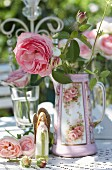 Vintage-style arrangement of roses, rose-patterned coffee jug and angel on table