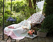 Comfortable seating area in garden with rose-patterned fabrics on lounger