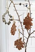 Braune Mürbeteigplätzchen in Blattform als Herbstdekoration an einem Ast hängend