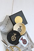 Hand-made foam rubber pineapple stamp, box with stamped motif and printed picture with golden circle lying on grey cloth