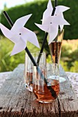 Hand-made windmills on drinking straws decorating glasses for garden party