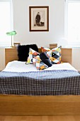 Double bed with headboard, geometrically patterned scatter cushions and checked bedspread below framed vintage photo of child on wall