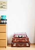 Stack of vintage suitcases next to chest of drawers with round boxes on top