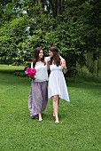 Two barefoot young women walking arm-in-arm across summer meadow, one holding bouquet of roses