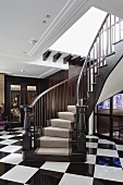 Foyer with elegantly curved staircase and black and white chequered floor