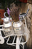 White vintage bike decorated with old milk churns and lavender