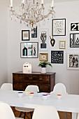 Essplatz mit weißem Tisch und Klassiker Schalenstühle vor Antikkommode, darüber Bildersammlung